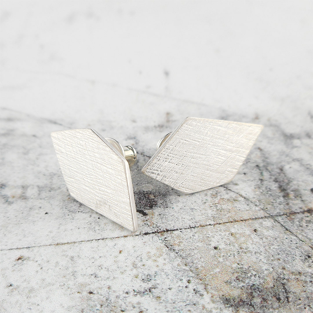 geometric silver stud earrings with a scratched texture