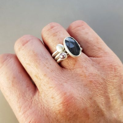 Grey sapphire, mauve freshwater pearl and hand cast silver pebble stacking rings in brushed silver